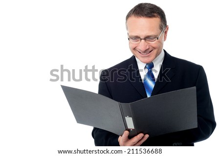 Aged businessman wearing glasses, reading a business report - stock photo