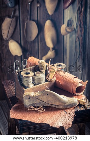 Aged cobbler workplace with tools, leather and shoes - stock photo
