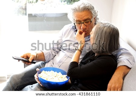 Aged couple eating popcorn and watching tv - stock photo