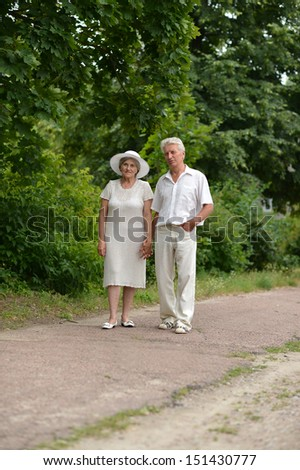 Aged couple is having a walk in green summer park