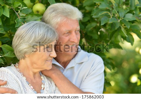 Aged couple is having fun in green summer park