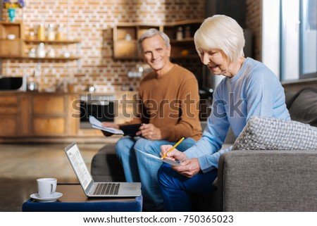 Aged couple. Nice serious retired man sitting on the sofa and holding some documents while looking at his wife