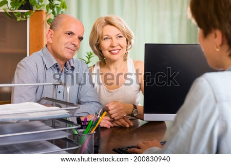 aged couple of pensioners talking with employee at office - stock photo