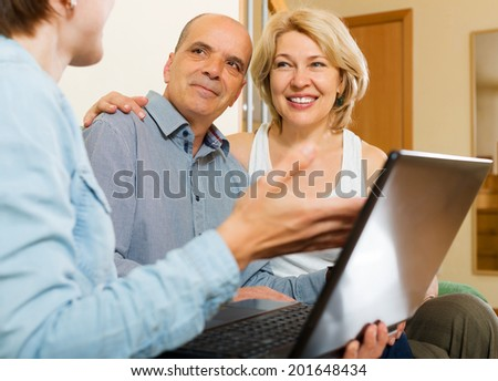 Aged couple talking with employee with laptop at home - stock photo