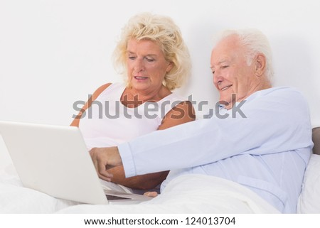 Aged couple using a laptop on the bed - stock photo