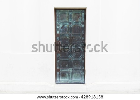 Aged dark blue metal door with white wall background - stock photo