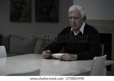 Aged depressed man and his lonely dinner - stock photo