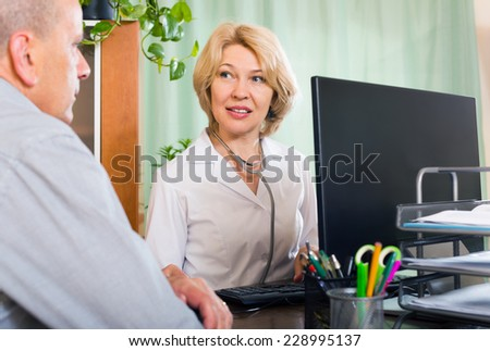Aged doctor talking with elderly male patient in clinic office