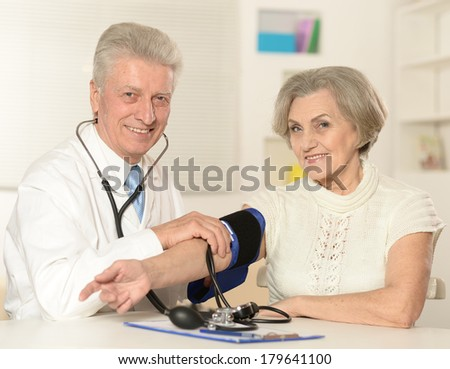 Aged doctor with a elderly patient in his office measuring pressure