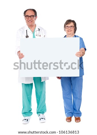 Aged doctors together displaying white billboard. Full length shot