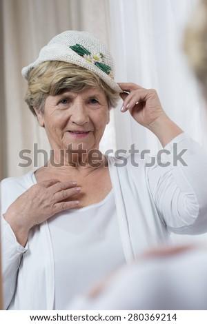 Aged elegant lady trying on new spring hat - stock photo