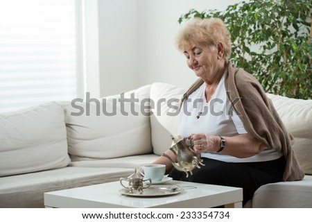 Aged elegant woman drinking her afternoon tea - stock photo
