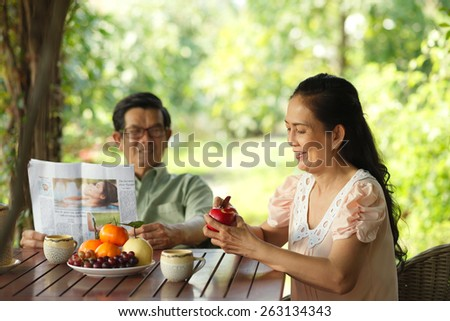 Aged family breakfast: woman peeling an apple while her husband reading a newspaper