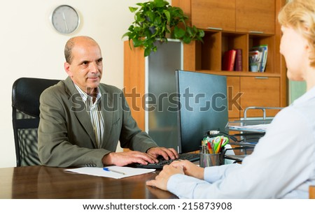 Aged female client talking with manager in notary's office - stock photo