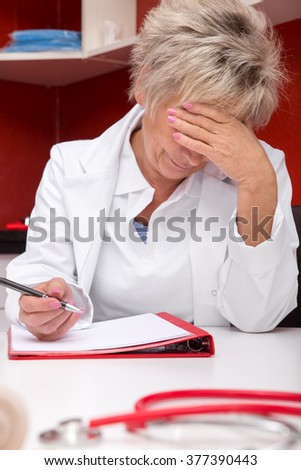 aged female doctor is stressed, documents on a table