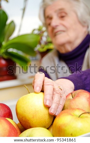 Aged female want to eat  apple - stock photo