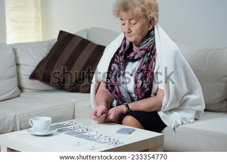 Aged focused woman playing cards in her apartment - stock photo