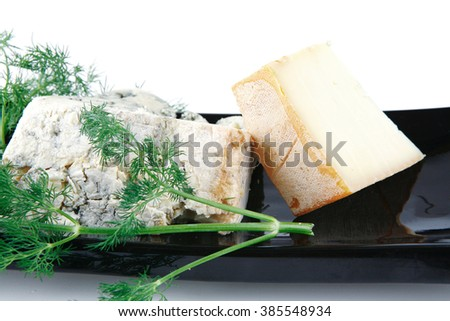 aged french delicatessen cheeses on black porcelain plate - stock photo