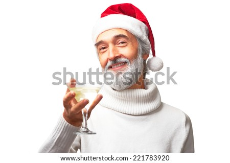 Aged handsome man in santa's red hat is going to drink martini smiling isolated on white background - stock photo