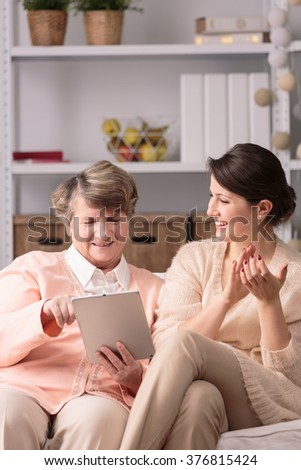 Aged happy woman learning to use tablet