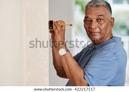 Aged Indian man using spirit level at home