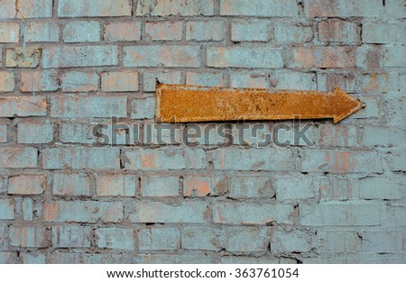 Aged industrial brick wall with rusty arrow.  - stock photo