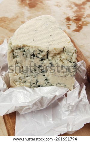 aged italian deli fresh blue stilton cheese and rye ciabatta served on wooden cutting plate on used baking paper as background - stock photo