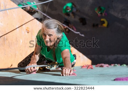 Aged Lady Doing Extreme Sport Elderly Female Makes Hard Move on Outdoor Climbing Wall Sporty Clothing on Fitness Training Intense but Positive Face Using Rope and Belaying Gear - stock photo