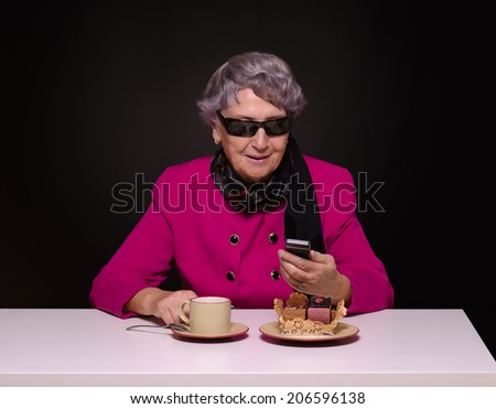 Aged lady in purple jacket sending message by mobile phone