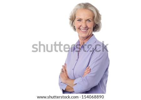 Aged lady posing to the camera with arms crossed - stock photo