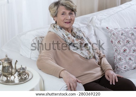 Aged lonely woman relaxing on white comfortable couch - stock photo