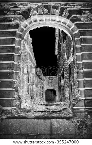 Aged luxury gloomy eerie tunnel hole with large dark grey arc in deserted obsolete brick estate abbey cloister home. Front view with space for text on black sky backdrop - stock photo