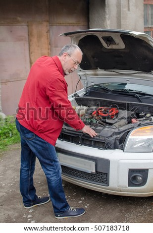 Aged man fixing the car on the street