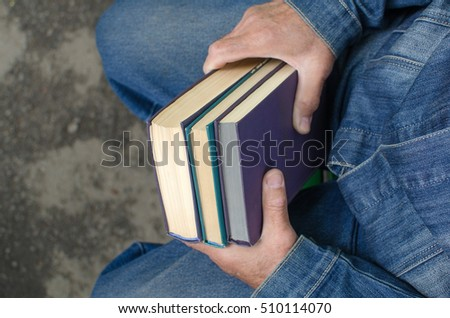 Aged man is holding books in his hands