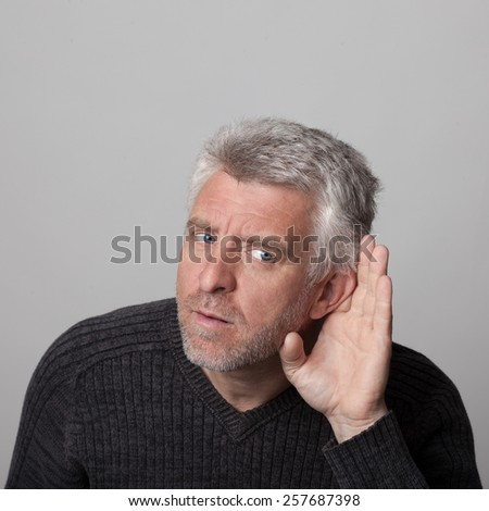 aged man listens with his hand to his ear