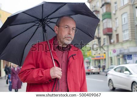 Aged man under the rain with umbrella