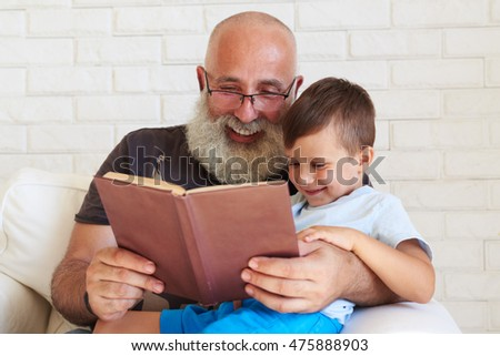 Aged man with white beard is reading a funny book to his grandson at home