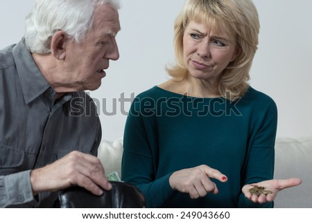 Aged married couple counting their savings - stock photo