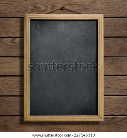 Aged menu blackboard hanging on wooden wall - stock photo