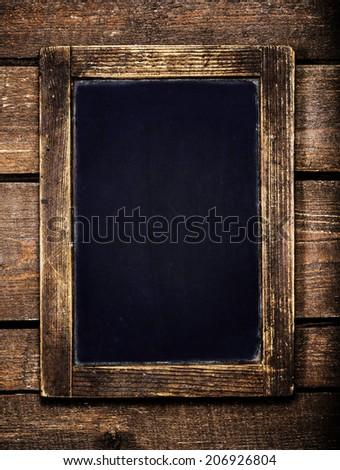 Aged  menu blackboard over vintage wooden background. Empty Chalkboard. - stock photo