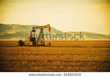 Aged Oil Pump on Colorado Prairie with Mountain Hills in the Background. Oil Industry Theme. - stock photo