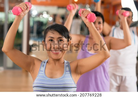 Aged people working out with dumbbells