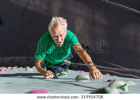 Aged Person Practicing Extreme Sport Elderly Male Climber Makes Hard Move on Outdoor Climbing Wall Sporty Clothing on Fitness Training Course Intense but Positive Face Using Rope and Belaying Gear  - stock photo