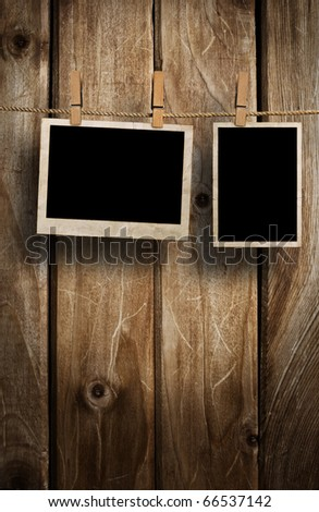 Aged photo frames on wood background - stock photo