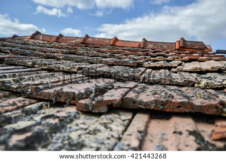Aged roofing tiles on old house in village on blue cloudy sky - stock photo