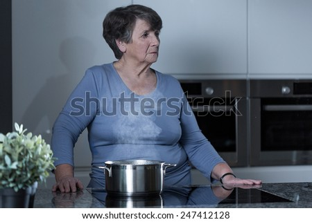 Aged sad woman cooking in the kitchen - stock photo