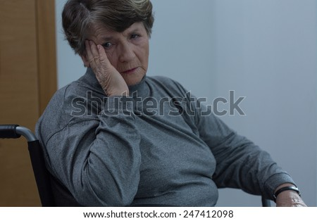 Aged sad woman on wheelchair in home - stock photo