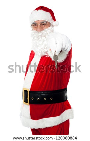 Aged Santa dangling a key. Unlock your X-mas gifts. - stock photo
