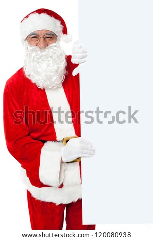Aged Santa holding blank white banner ad board. Standing beside - stock photo