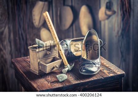 Aged shoemaker workplace with tools, leather and shoes - stock photo